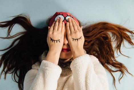 kvinde der holder hænderne for øjnene, hvor der er tegnet øjenvipper på hendes hænder