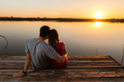 mand der sidder med armen om en kvinde på en badebro ved en sø