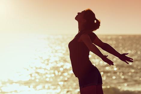 kvinde ved havet, der strækker armende tilbage og kroppen frem mod solen