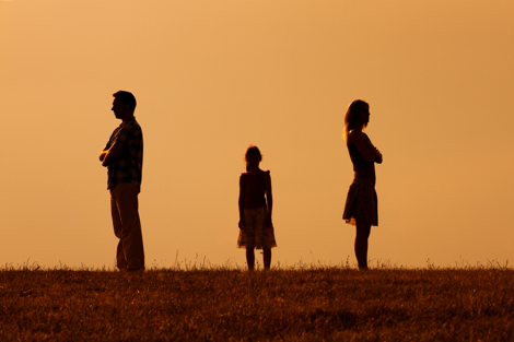 par der står med ryggen til hinanden og en ung pige der står i midten