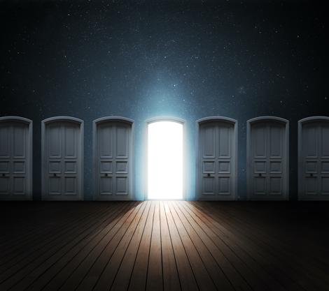 en væg med 7 døre hvor den midterste er åben og der strømmer lys ind